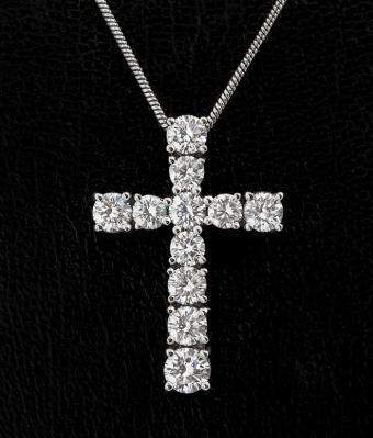 Colgante en forma de cruz con cadena en oro blanco de 18 kts.
