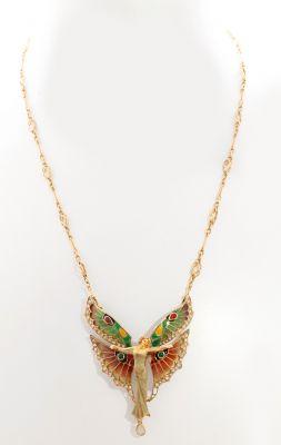 En oro amarillo de 18 kts. Modelo fantasía de marcado simbolismo romántico,  decorado con la figura de una ninfa de alas extendidas,