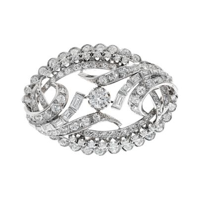 Brooch in 18 kt white gold, 1960s. With central diamond, brilliant cut, color H, VS purity, mounted on an almond body formed from diamonds lined waves, baguette and brilliant cut and triple diamond border, brilliant cut , color H, purity VS, crimped in mouths of different types.