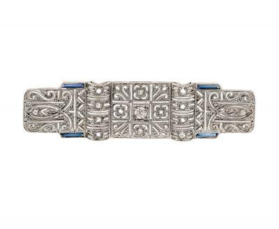 Broche-placa en oro blanco de 18 kts y vistas en platino. Con un diamante central,  talla brillante,  de peso ca.