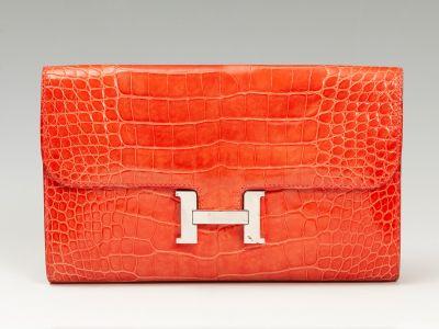 Cartera de mano HERMÈS Constance en piel de cocodrilo. De estructura alargada,  plana,  elegante y depurada de color naranja,.