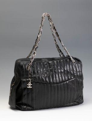 Bolso CHANEL en piel de color negro de acabado estriado con ribeteado en color blanco. Bolsillos exteriores en su frente y en su parte trasera.