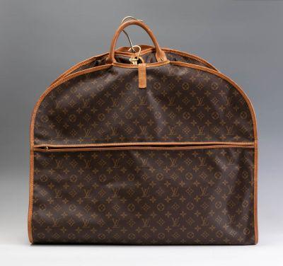 Portatrajes LOUIS VUITTON. Con los bordes,  el asa y la cremallera de cierre realizados en piel marrón,  y la conocida Lona Monogram,.