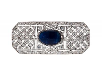 Broche realizado en oro blanco de 18 Kts de forma geométrica de pavé con 80 diamantes talla brillante con un peso total de 0,75 ctes, y un zafiro azul talla cabujón oval de 9x13 mm y un peso de 2,50 ctes.Cierre de pincho con seguro de cañón.