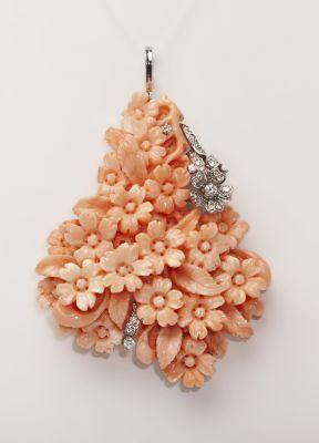 Colgante realizado en oro blanco de 18 Kts. con un grupo de coral rosa tallado en flores y hojas con mucho relieve.