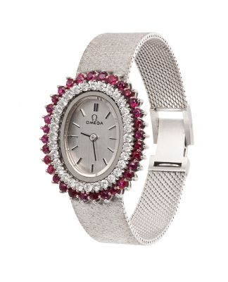 OMEGA women's watch in 18Kts white gold with an oval shape with a double oval. 32 rubies, rounded carving, weight of 0,96 ctes.